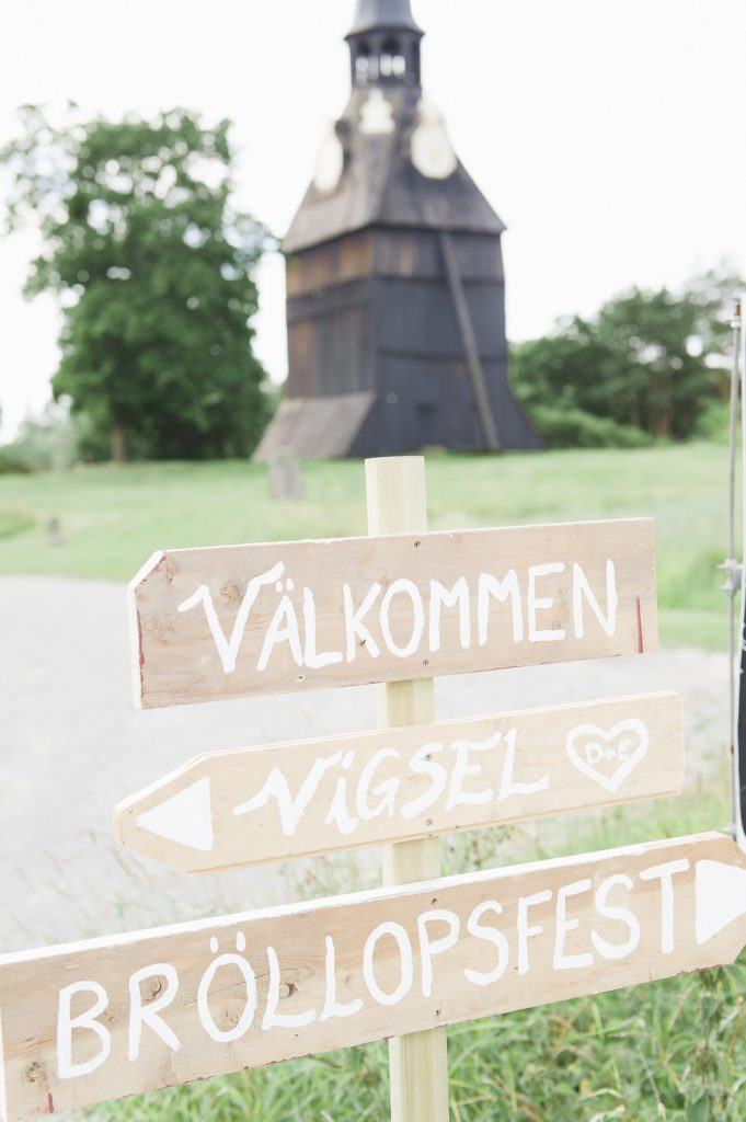Välkommenskylt framför klocktorn vid Veckholms kyrka