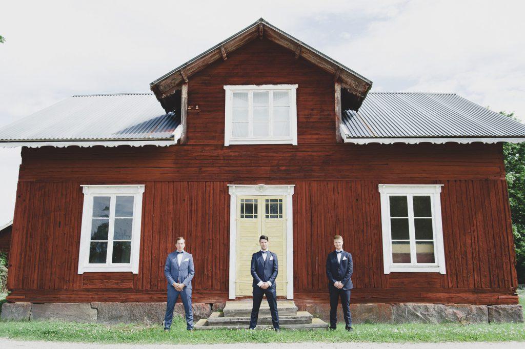 Brudgrum och hans två bestman framför ett rött hus i Hedsta, Veckholm