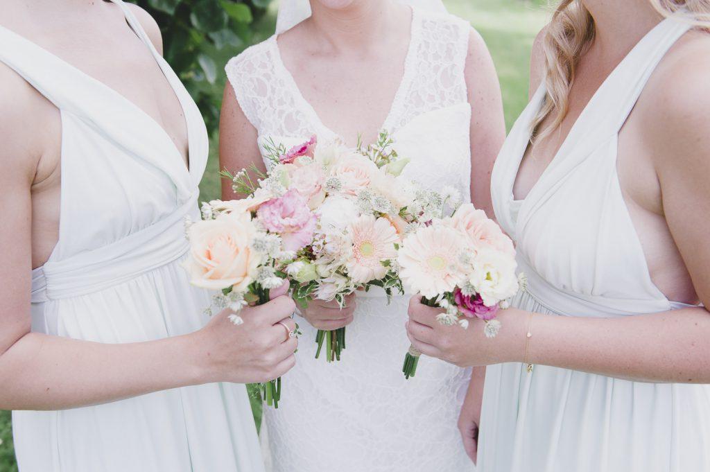 Bruden och tärnorna hålla i sina buketter
