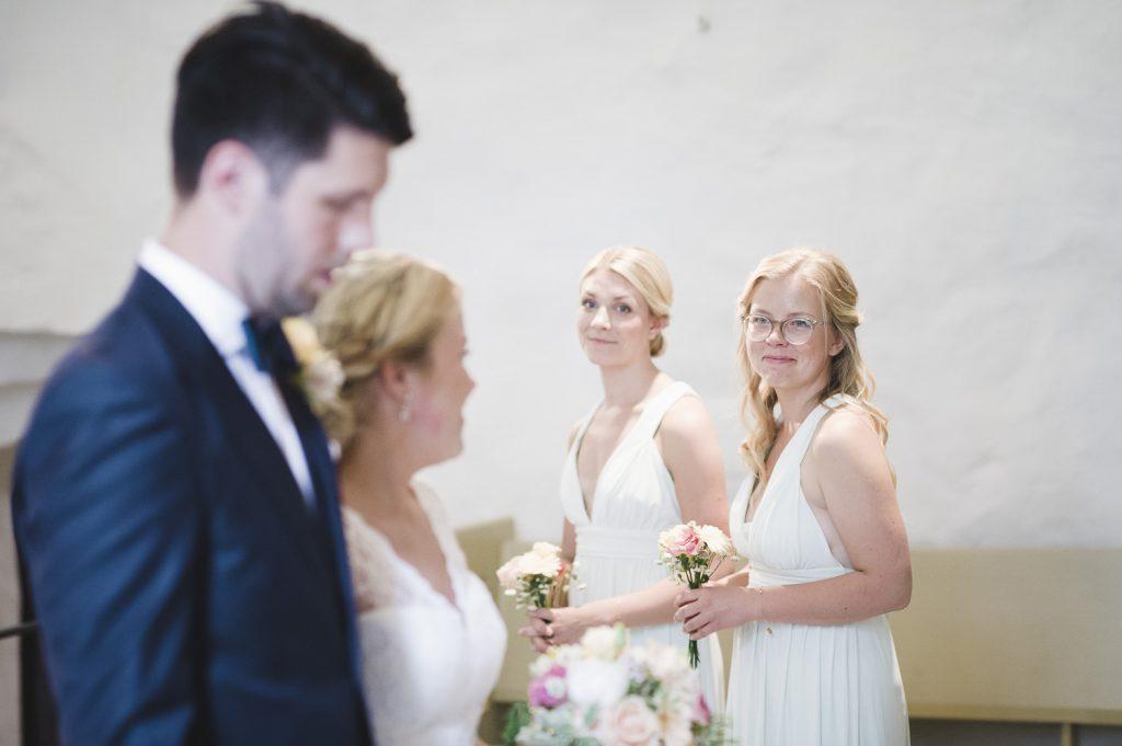 Bruden tittar på tärnorna under vigsel i Veckholms kyrka