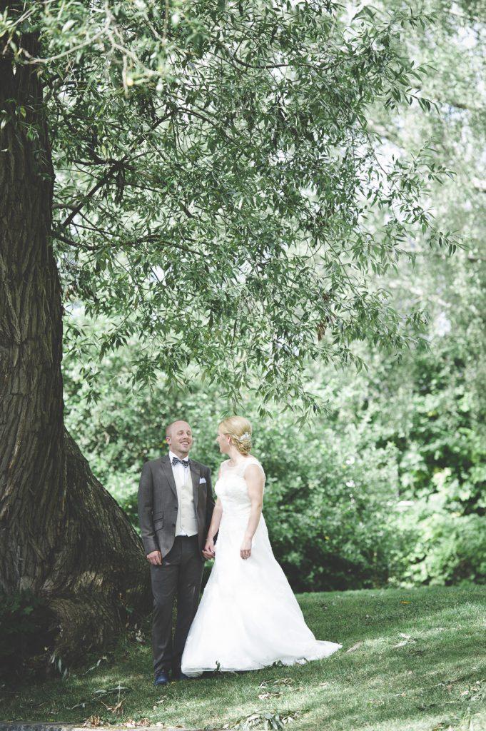 Brudparet i skuggan av ett träd