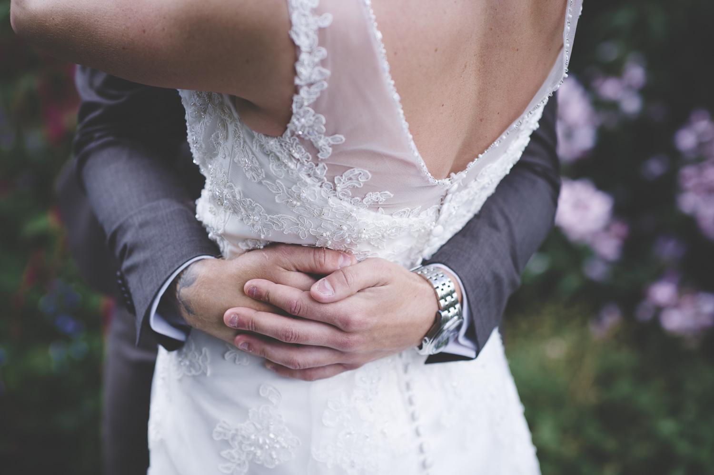 Brudparet håller om varandra under parfotograferingen