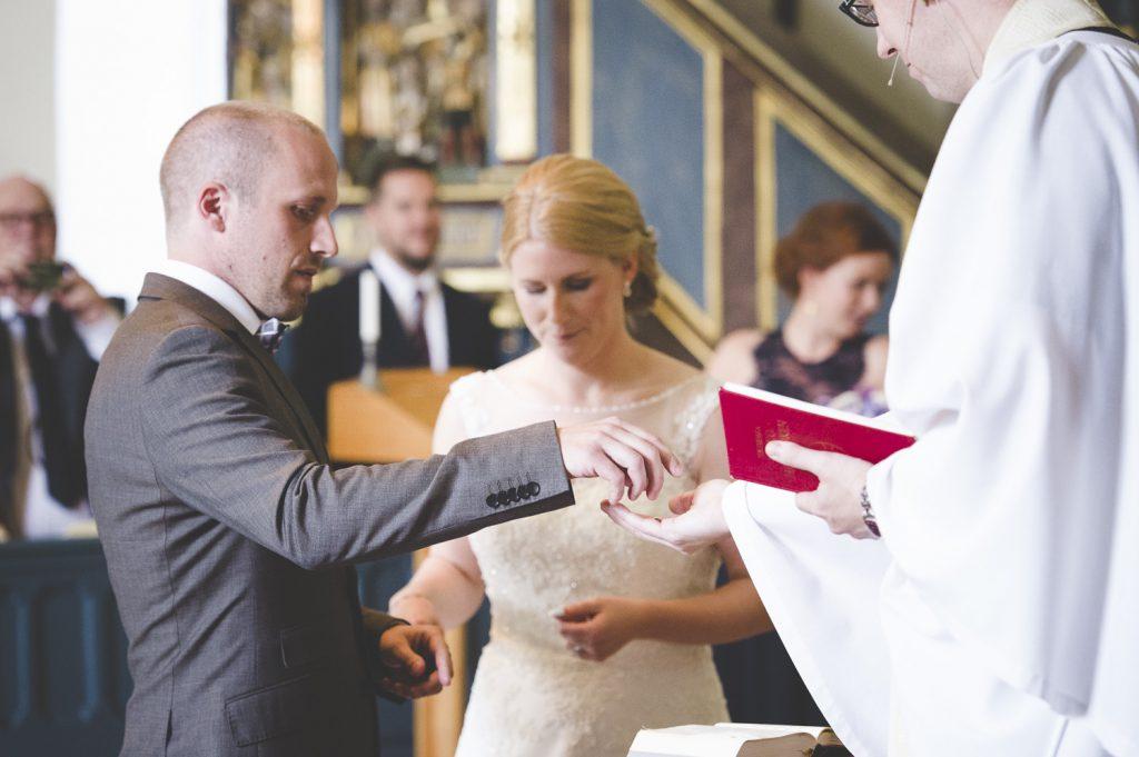 Brudgrummen lämnar ringarna till prästen