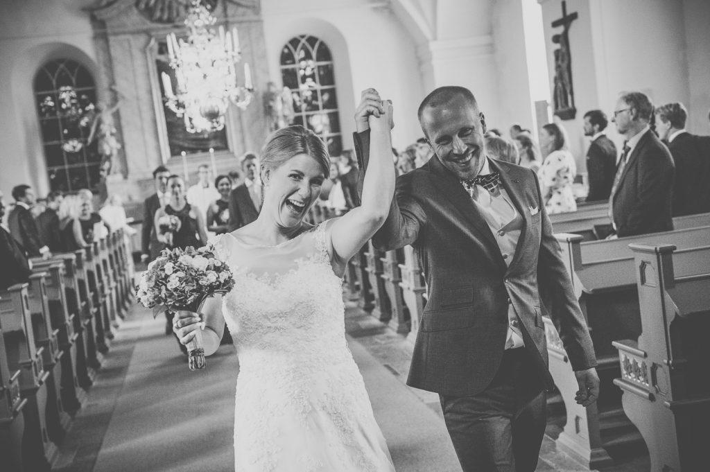 Brudparet är glada under utgång från Tillinge kyrka