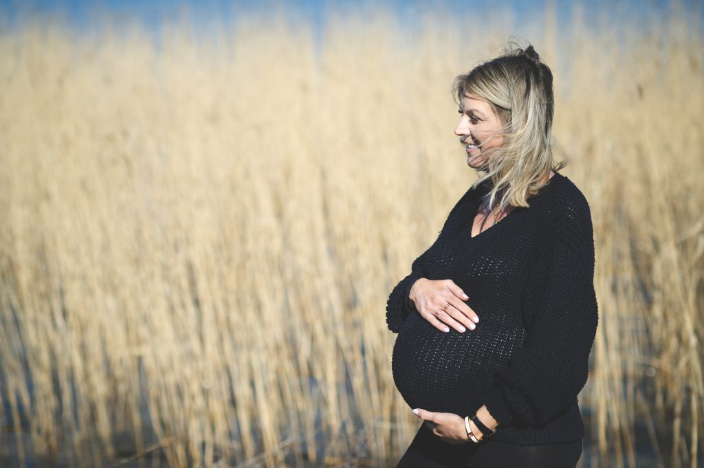 Gravid kvinna håller om sin mage framför Mälaren