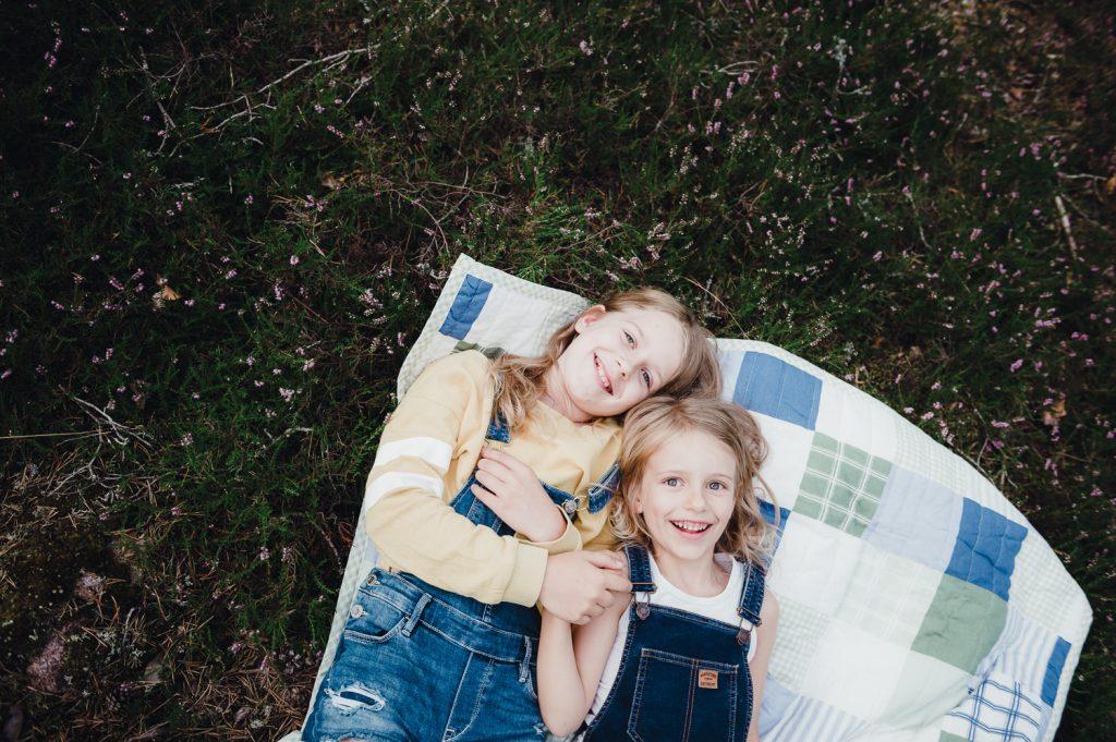 Syskonfotografering med systrar som ligger på filt bland ljung