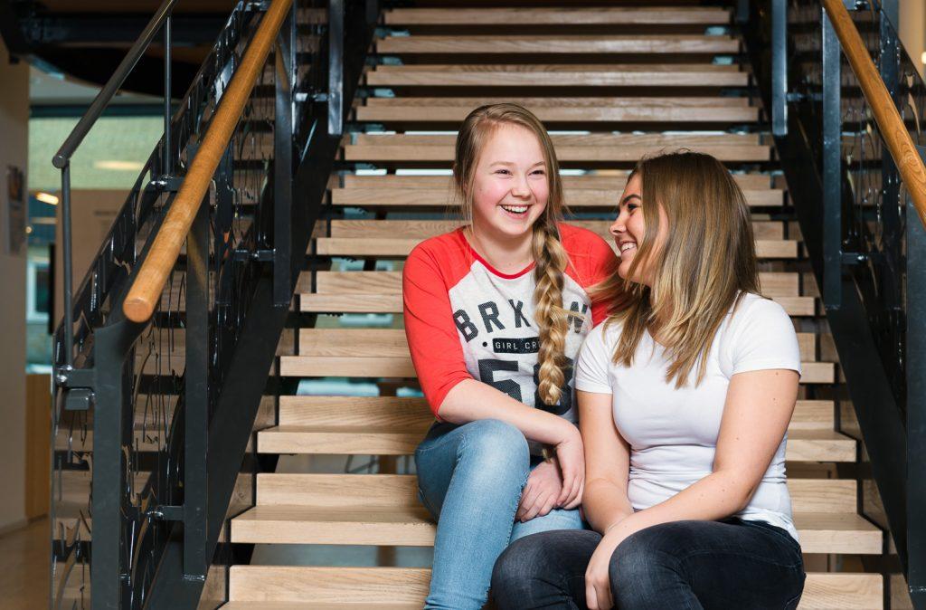 Två tjejer sitter i en trappa på ett bibliotek och skrattar