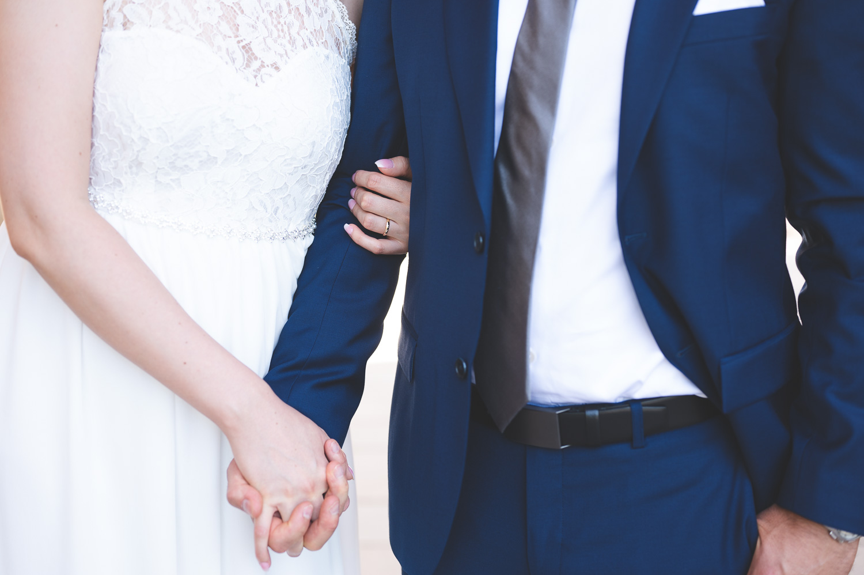Brud och brudgum håller varandra i händerna